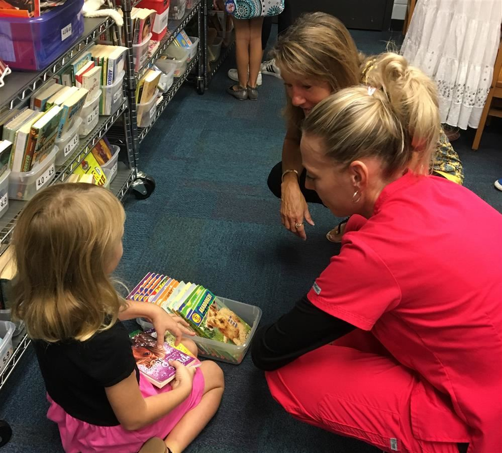adults helping child choose book to read